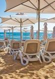 Rangées des chaises étendues/des recliners/des lits pliants en plastique de salon sur une plage sablonneuse d'or Images libres de droits