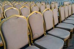 Rangées des chaises en bois dures traditionnelles avec le coussin et le golde mous photo stock