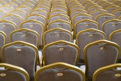 Rangées des chaises en bois dures traditionnelles avec le coussin et le golde mous image libre de droits