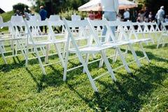 Rangées des chaises pliantes blanches sur la pelouse image stock