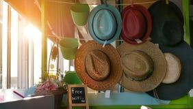 Rangées des chapeaux de paille multicolores à vendre sur des étagères sur un marché Photo libre de droits