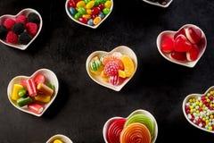 Rangées des cuvettes en forme de coeur en céramique avec des sucreries Photos libres de droits
