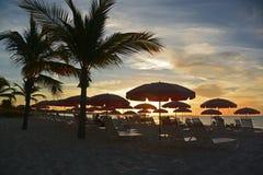 Rangées des parapluies et des chaises de plage chez le coucher du soleil, les Turcs et la Caïques Images libres de droits