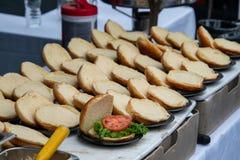 Rangées des petits pains d'hamburger ouverts sur une table Seulement un a eu la laitue et une tranche de tomate là-dessus images stock