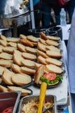 Rangées des petits pains d'hamburger ouverts sur une table Seulement un a eu la laitue et une tranche de tomate là-dessus photo libre de droits