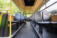 Rangées des sièges gris à l'intérieur de la salle claire de l'autobus vide de ville Images stock