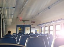 Rangées des sièges mous bleus dans une voiture du train de voyageurs Le soleil lumineux brille par la fen?tre photographie stock libre de droits