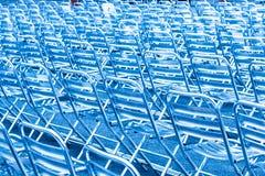 Rangées des sièges vides de chaise en métal dans la lumière bleue Photos stock