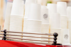 Rangées des tasses blanches à l'envers de carton pour des boissons, vaisselle jetable pour le caffee, pièce en t, inexistant abst Images libres de droits
