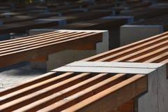 Rangées diagonales des bancs de conception simple faits de bois et béton photographie stock libre de droits