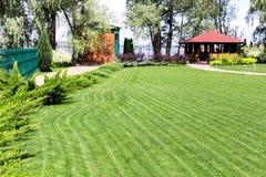 Rangées fraîchement fauchées de pelouse verte à la résidence de pays avec le pavillon Haie des cèdres frais Conception de paysage photo libre de droits