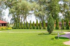 Rangées fraîchement fauchées de pelouse verte à la résidence de pays avec le pavillon Haie des cèdres frais Conception de paysage images libres de droits