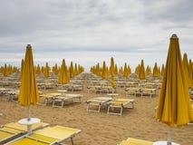 Rangées grandes-angulaires de vue des canapés jaunes du soleil sur une plage Photos stock