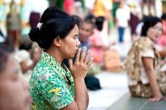 RANGÚN, MYANMAR - 29 DE ENERO: Los devotos de WomanBuddhist ruegan en Shwedagon templo el 29 de enero de 2010 Myanmar Foto de archivo libre de regalías