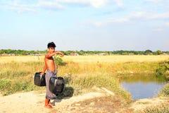 RANGÚN, MYANMAR - 25 de noviembre de 2015: Portador de agua con dos cubos Fotografía de archivo