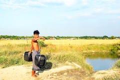 Rangún, Myanmar - 18 de noviembre de 2015: Portador de agua con dos cubos que consiguen el agua en el campo Fotografía de archivo