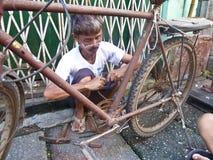 RANGÚN, MYANMAR - 1 de octubre de 2013 - un reparador de la bicicleta fija Fotos de archivo
