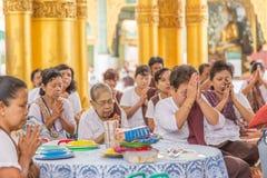RANGÚN, MYANMAR - UNE 22, 2015: La gente de Myanmar ruega a Buda i Imagen de archivo libre de regalías