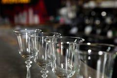 Rang?e des verres propres vides sur le compteur dans la barre photos stock
