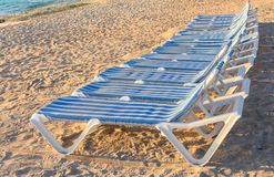 Range of blue and white striped lounge chairs on a sandy beach with blue ocean in the background. Royalty Free Stock Photography