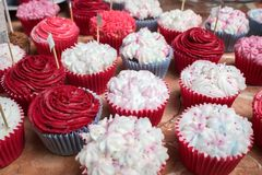 Bright cupcakes with pink and white frosting at a banquet. A range of bright tasty cupcakes at reception, raspberry and vanilla Royalty Free Stock Photography
