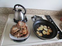 Range with cooked potato, pot and plate with meat. stock photo