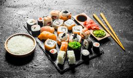 The range of different types of sushi, rolls and Maki with sauces and chopsticks. On black rustic background stock photos