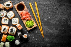 The range of different types of sushi, rolls and Maki with sauces and chopsticks. On black rustic background royalty free stock images