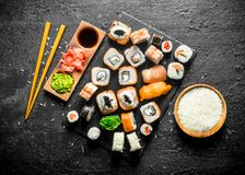 The range of different types of sushi, rolls and Maki with sauces and chopsticks. On black rustic background royalty free stock photo
