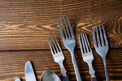 A range of different vintage Cutlery with knives, forks and spoons viewed from above on a textured wooden background. Close up royalty free stock images
