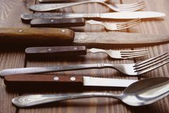 A range of different vintage Cutlery with knives, forks and spoons viewed from the side on a textured wooden background. royalty free stock photo