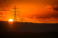 Sunset over high voltage pillars Stock Photos