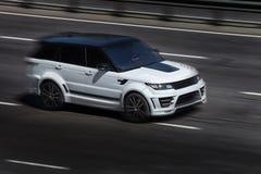 Range Rover едет на дороге Против предпосылки запачканных деревьев стоковая фотография rf