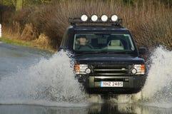 Range Rover que conduce a través de los caudales de una crecida BRITÁNICOS Foto de archivo libre de regalías