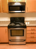 Range, stove, and microwave and kitchen cabinets Royalty Free Stock Photos