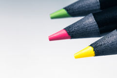 Range of three black wooden colour pencils on white background. With copy space royalty free stock photo