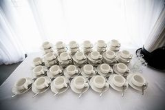A range of traditional clean empty ceramic coffee cups on the table in the restaurant. Lots of white cups on saucers for serving. Tea or coffee for Breakfast stock image