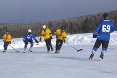 Men`s teams compete in a Pond Hockey Festival in Rangeley. Rangeley, Maine, USA - February 4, 2017: Men`s teams compete on the ice at the 11th annual New Royalty Free Stock Photo