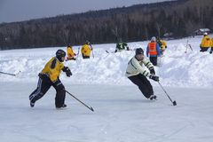Men`s teams compete in a Pond Hockey Festival in Rangeley. Rangeley, Maine, USA - February 4, 2017: Men`s teams compete on the ice at the 11th annual New Stock Images