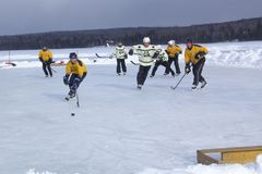 Men`s teams compete in a Pond Hockey Festival in Rangeley. Rangeley, Maine, USA - February 4, 2017: Men`s teams compete on the ice at the 11th annual New Stock Photo