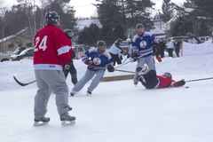 Men`s teams compete in a Pond Hockey Festival in Rangeley. Rangeley, Maine, USA - February 4, 2017: Men`s teams compete on the ice at the 11th annual New Royalty Free Stock Image