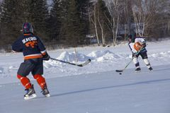 Women`s teams compete in a Pond Hockey Festival in Rangeley. Rangeley, Maine, USA - February 4, 2017: Women`s teams compete on the ice at the 11th annual New Stock Photo
