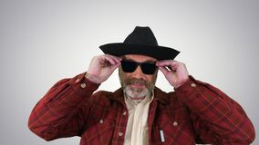 Ranger in a cowboy hat putting on sunglasses and smiling to camera on gradient background.