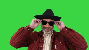 Ranger in a cowboy hat putting on sunglasses and smiling to camera on a Green Screen, Chroma Key.