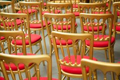 Ranges of empty golden red chairs. Closeup shot stock photography