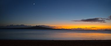 Rangitoto Island at Dawn Panorama. A panoramic view of a new day as the sun rises behind Rangitoto Island, Auckland, New Zealand Stock Photos
