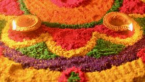 Rangoli with glowing diyas. Rangoli colors in the background with illuminated oil lamps or deepaks on occasion of diwali festival in India Stock Photos