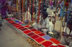 Rangoli-Farbverkäufer, der Farbpulver in Sonntags-Markt verkauft stockfotografie