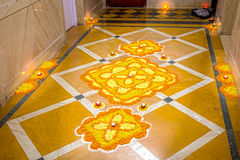 Rangoli. Floral orange and yellow rangoli decorated with Diyas to celebrate Diwali Stock Photo