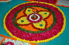 Rangoli art India. Rangoli kolam or muggu is a folk art from India. Rangoli made of beautiful colorful flowers. Done during Diwali, Onam, Pongal and other Indian Stock Image